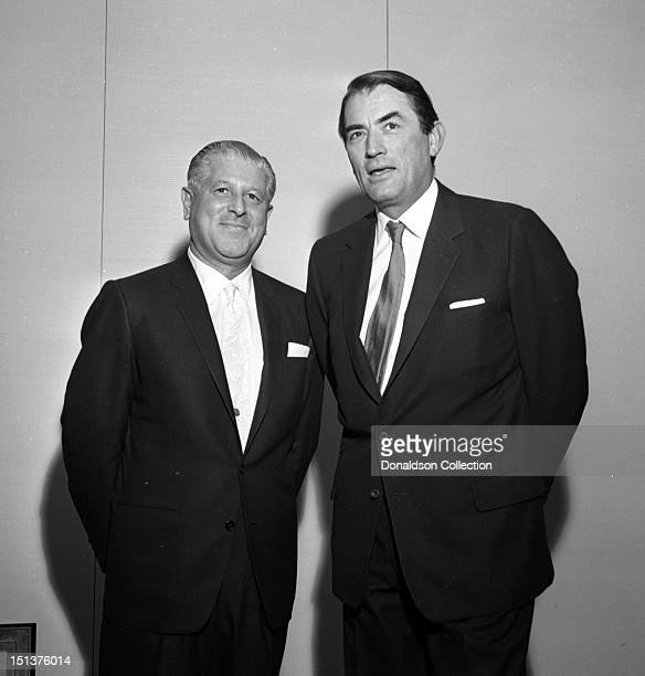 Actor Gregory Peck poses for a portrait with another man at a dinner for the Motion Picture Pioneers Association at the Playboy Club on November 19...