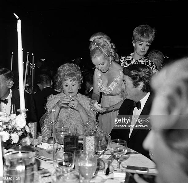 Actor Gregory Peck sits with actress Lucille Ball and actress Debbie Reynolds during an event in Los AngelesCA