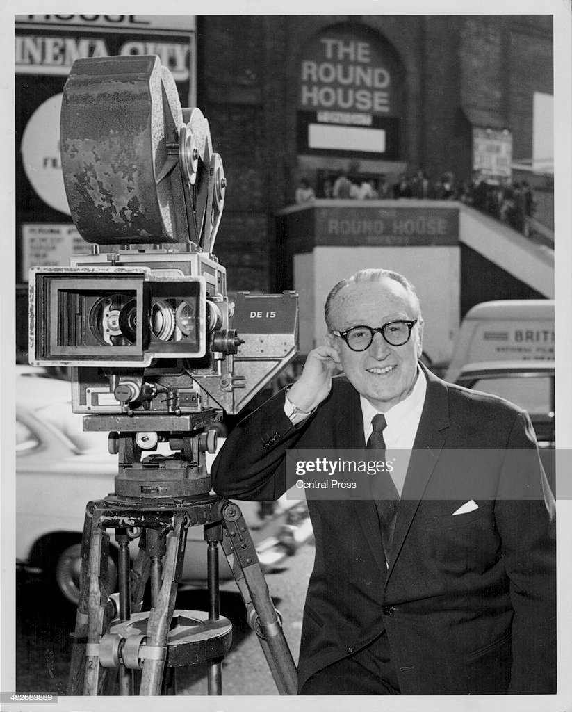 Actor Harold Lloyd posing with one of the first color cinecameras at the 'Cinema City' exhibition at the Roundhouse London September 22nd 1970