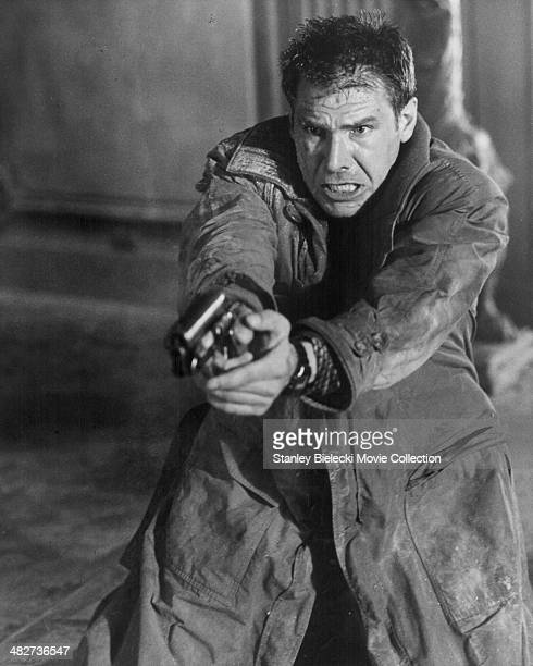 Actor Harrison Ford holding a gun in a scene from the movie 'Blade Runner' 1982