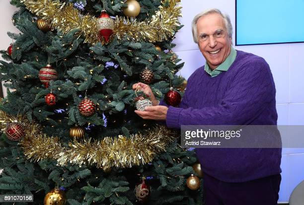 Actor Henry Winkler poses for photos next to a Christmas tree at the SiriusXM studios on December 12 2017 in New York City