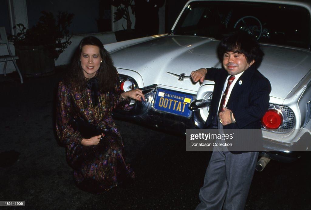 Actor <a gi-track='captionPersonalityLinkClicked' href=/galleries/search?phrase=Herve+Villechaize&family=editorial&specificpeople=1691626 ng-click='$event.stopPropagation()'>Herve Villechaize</a> attends an event with a woman and his car that has the license plate OOTTAT a play on his name 'Tatu' from the TV show 'Fantasy Island' in circa 1980 in Los Angeles, California.