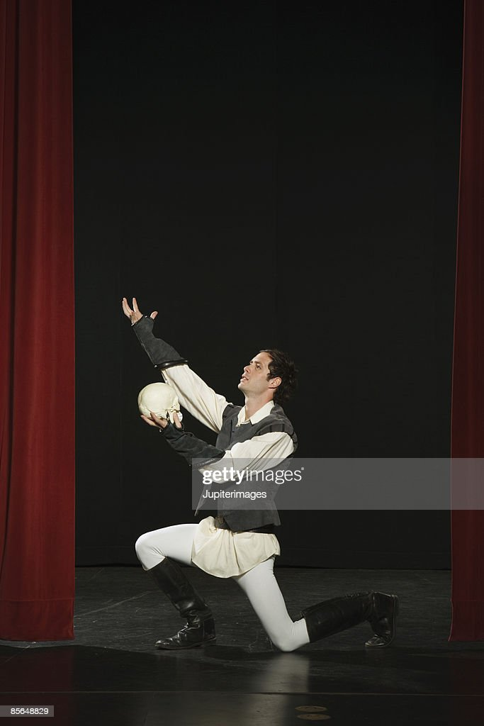 Actor holding skull and performing on stage