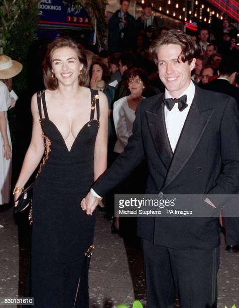 Actor Hugh Grant star of 'Four Weddings and a Funeral' arrives for the charity premiere of the film with his girlfriend actress Elizabeth Hurley at...
