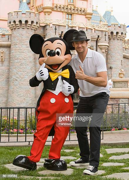 Actor Hugh Jackman poses with Mickey Mouse outside Sleeping Beauty Castle at Disneyland April 23 2009 in Anaheim California