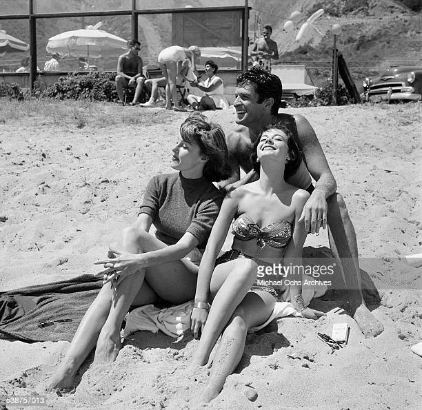 Actor Hugh O'Brian sits with actresses Elaine Stewart and Natalie Wood during the Thalians Beach Ball in MalibuCalifornia
