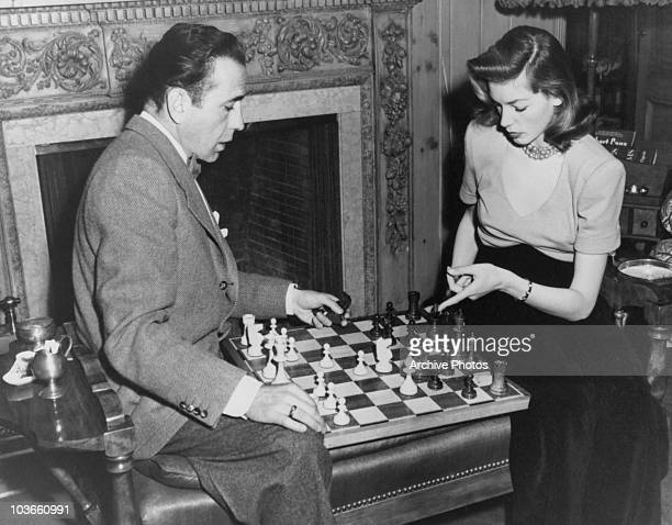 Actor Humphrey Bogart and his wife actress Lauren Bacall pictured playing chess USA circa 1955