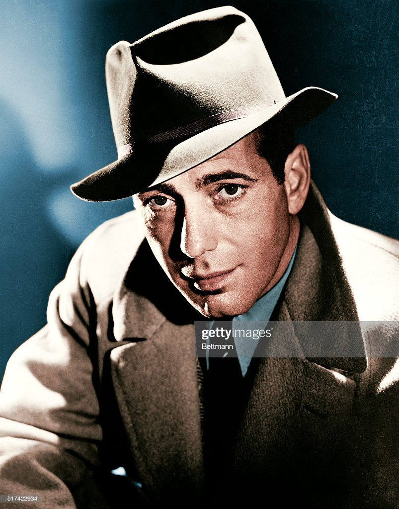 Actor Humphrey Bogart wearing a fedora hat and overcoat.