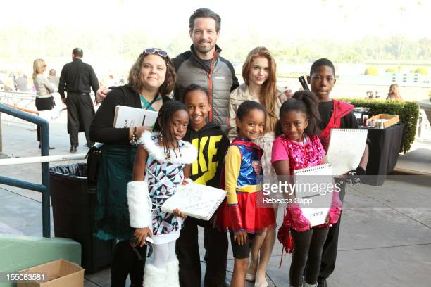 Actor Ian Bohen and actress Holland Roden take photos with kids at Children Mending Hearts Kids' Breakfast at the Track Event at Santa Anita Park on...