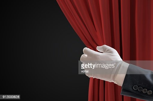 Actor is pulling red curtains in theatre with hand. : Stock Photo
