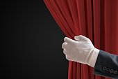 Actor is pulling red curtains in theatre with hand.
