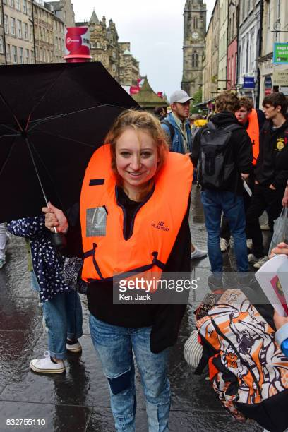 Actor Issy Crutchley wears a lifejacket and carries an umbrella in the rain during the Edinburgh Festival Fringe to promote a show 'The Runner' which...