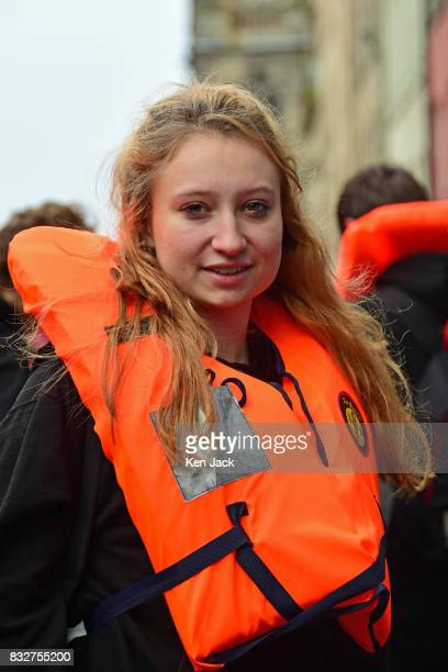 Actor Issy Crutchley wears a lifejacket on the Royal Mile during the Edinburgh Festival Fringe to promote a show 'The Runner' which tells the story...