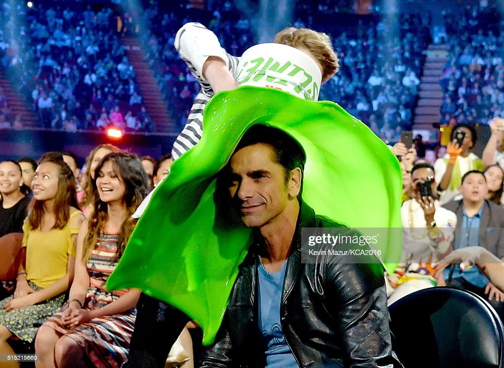 Actor Jace Norman pours a bucket of slime on actor John Stamos during Nickelodeon's 2016 Kids' Choice Awards at The Forum on March 12 2016 in...
