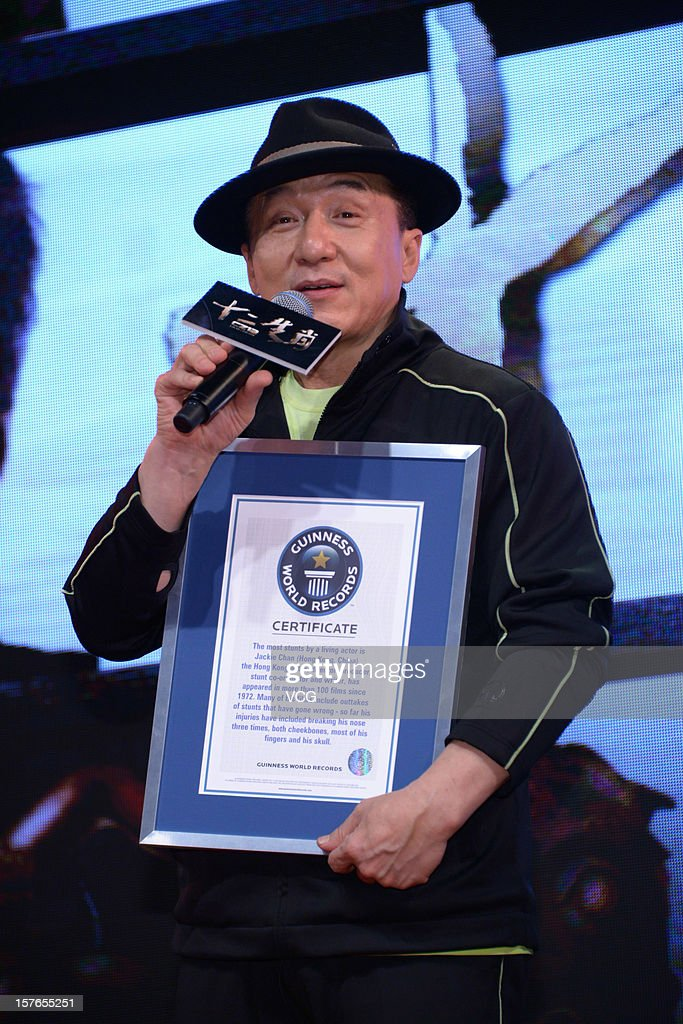 Actor Jackie Chan holds a Guinness World Records certificate for the most stunts by a living actor, presented to him during a press conference for 'Chinese Zodiac' at Jackie Chan Museum on December 5, 2012 in Shanghai, China. The certificate outlines that actor, director, producer, stunt co-ordinator and writer Jackie Chan has appeared in over 100 films since 1972 and that injuries sustained so far whilst performing stunts include breaking his nose three times. both cheekbones, most of his fingers and his skull.