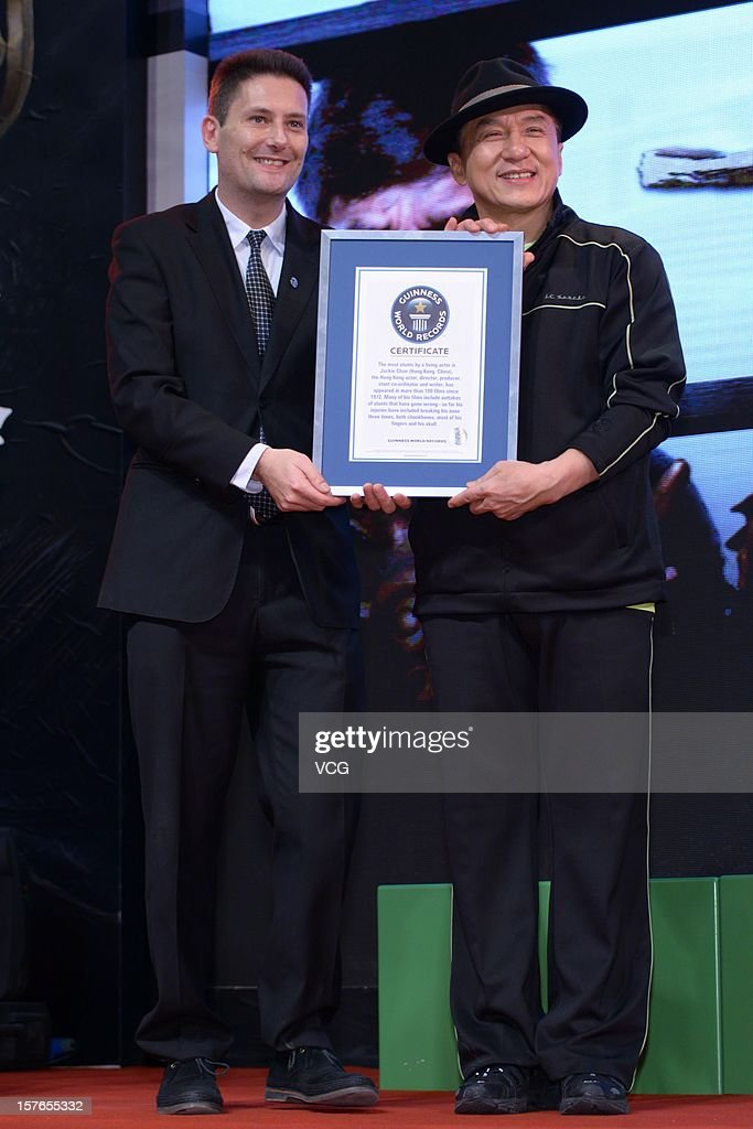 Actor Jackie Chan (R) is presented with a Guinness World Records certificate for the most stunts by a living actor during a conference for 'Chinese Zodiac' at Jackie Chan Museum on December 5, 2012 in Shanghai, China. The certificate outlines that actor, director, producer, stunt co-ordinator and writer Jackie Chan has appeared in over 100 films since 1972 and that injuries sustained so far whilst performing stunts include breaking his nose three times, both cheekbones, most of his fingers and his skull.