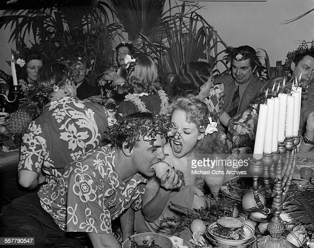 Actor Jackie Coogan is fed by his wife actress Betty Grable as Ken Murray looks on during a party in Los Angeles California