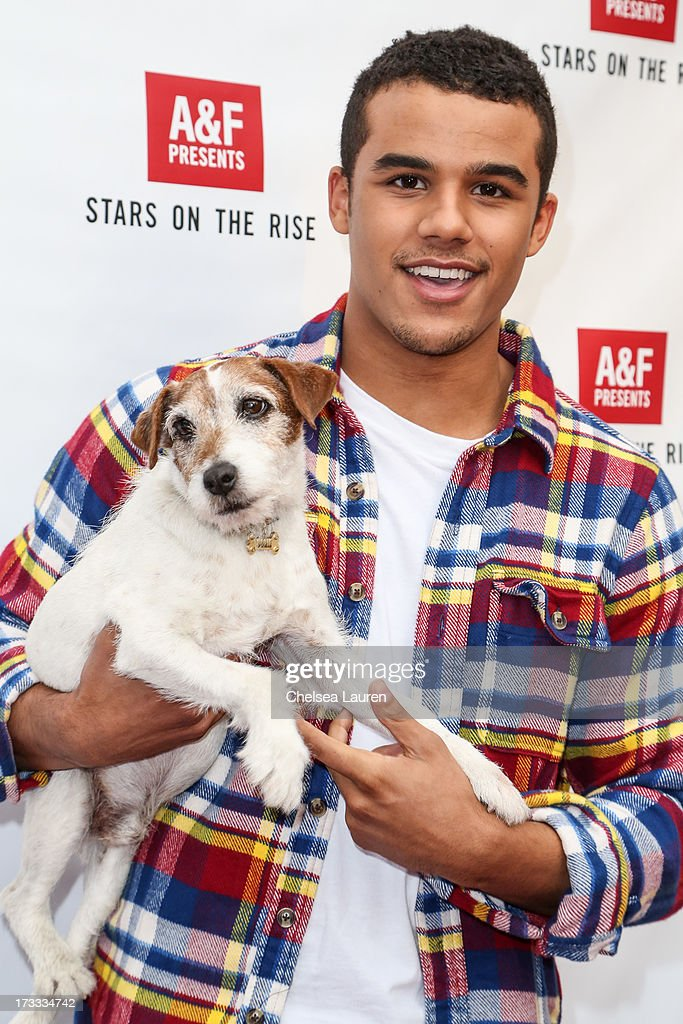 Actor Jacob Artist (R) and actor dog Uggie attend Abercrombie & Fitch's 'Stars on the Rise' event at Abercrombie & Fitch on July 11, 2013 in Los Angeles, California.