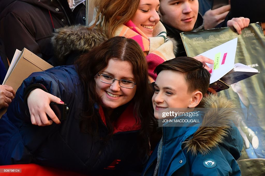 US actor Jaeden Lieberher poses for a photo with a fan as he arrives for a photo call for the film ' Midnight Special by Jeff Nichols' screened in competition of the 66th Berlinale Film Festival in Berlin on February 12, 2016. / AFP / John MACDOUGALL