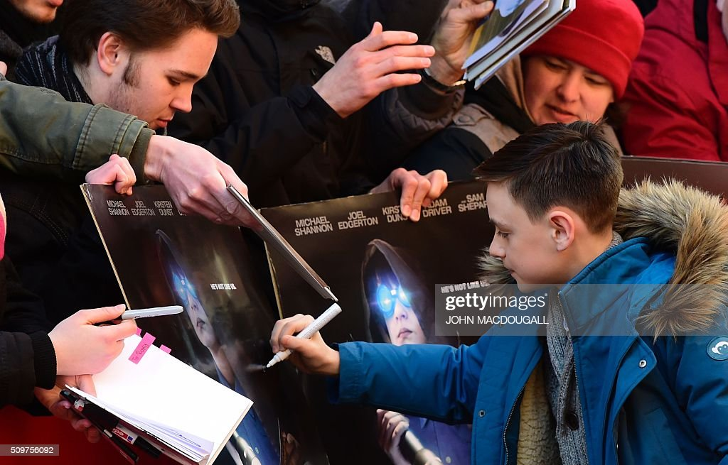 US actor Jaeden Lieberher signs autographs as he arrives for a photo call for the film ' Midnight Special by Jeff Nichols' screened in competition of the 66th Berlinale Film Festival in Berlin on February 12, 2016. / AFP / John MACDOUGALL