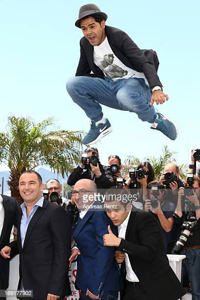 Actor Jamel Debbouze jumps over director Mohamed Hamidi and actors Fatsah Bouyahmed and Malik Bentalha at the 'Ne Quelque Part' Photocall during The...