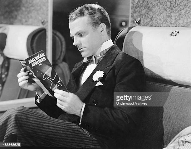Actor James Cagney reading the safety brochure aboard an American Airlines plane Hollywood California mid 1930s