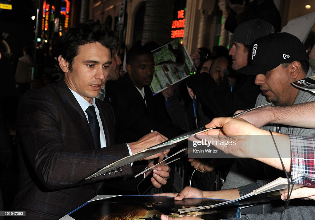 Actor <a gi-track='captionPersonalityLinkClicked' href=/galleries/search?phrase=James+Franco&family=editorial&specificpeople=577480 ng-click='$event.stopPropagation()'>James Franco</a> signs autographs for fans at the world premiere of Walt Disney Pictures' 'Oz The Great And Powerful' at the El Capitan Theatre on February 13, 2013 in Hollywood, California.