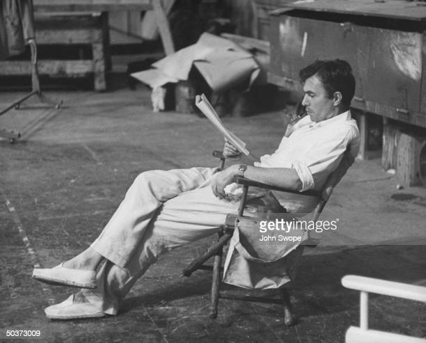 Actor James Mason dressed in white oxford shirt white linen pants and espadrilles reading script on set during filming of Julius Caesar