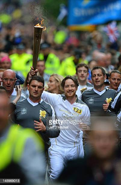 Actor James Mcavoy runs down Buchanan Street carrying the Olympic Torch during the leg between Stranrear and Glasgow on June 8 2012 in Glasgow...