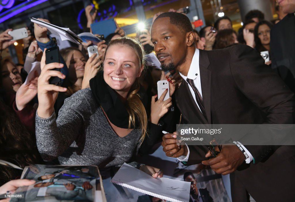 Actor <a gi-track='captionPersonalityLinkClicked' href=/galleries/search?phrase=Jamie+Foxx&family=editorial&specificpeople=201715 ng-click='$event.stopPropagation()'>Jamie Foxx</a> signs autographs for fans as he attends the 'White House Down' Germany premiere at CineStar on September 2, 2013 in Berlin, Germany.