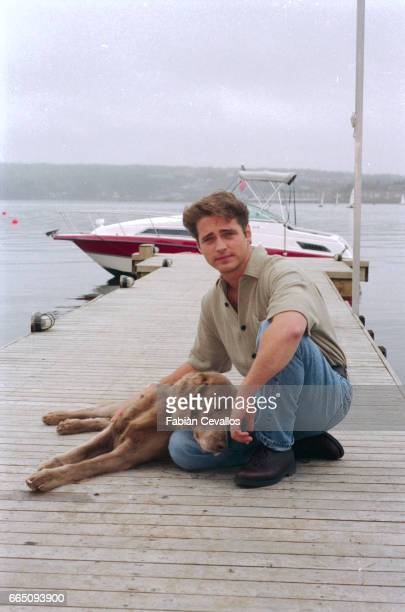 Actor Jason Priestley wearing a beige shirt and blue jeans poses with a dog in front of a motorboat on the set of the movie Life and Death on Long...