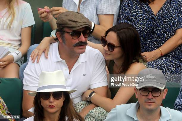 Actor Jean Dujardin and Nathalie Pechalat watches on from Court Philippe Chatrier during the mens singles final match between Rafael Nadal of Spain...