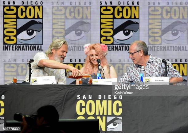 Actor Jeff Bridges pours shots for screenwriter Jane Goldman and writer/executive producer Dave Gibbons onstage at the 20th Century FOX panel during...