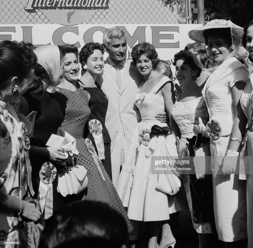 Actor Jeff Chandler poses with Miss Universe Contestants in Los Angeles, California.