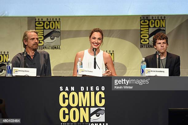 Actor Jeremy Irons actress Gal Gadot and actor Jesse Eisenberg from 'Batman v Superman Dawn of Justice' attend the Warner Bros presentation during...