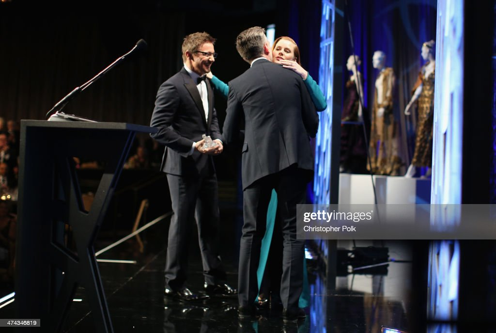 Actor Jeremy Renner, costume designer Michael Wilkinson and honoree Amy Adams onstage during the 16th Costume Designers Guild Awards with presenting sponsor Lacoste at The Beverly Hilton Hotel on February 22, 2014 in Beverly Hills, California.