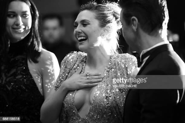 US actor Jeremy Renner US actress Elizabeth Olsen and US actress Julia Jones pose as they arrives on May 20 2017 for the screening of the film 'Wind...
