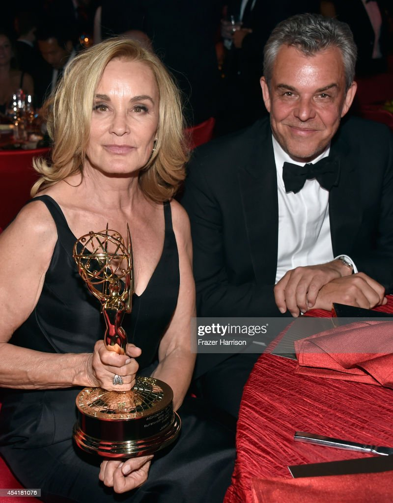 Actor Jessica Lange winner of the 'Outstanding lead in a miniseries or a movie' award for American Horror Story:Coven (L) and actor John Huston attend the 66th Annual Primetime Emmy Awards Governors Ball held at Los Angeles Convention Center on August 25, 2014 in Los Angeles, California.