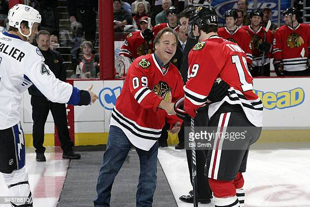 Actor Jim Belushi shakes hands with team captains Jonathan Toews of the Chicago Blackhawks and Vincent Lecavalier of the Tampa Bay Lightning on...