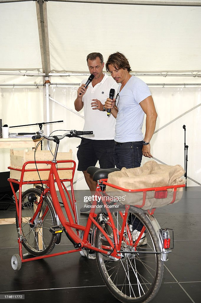 Actor Joachim Kretzer and actor Hakim Michael are beeing pictured on the famous red bike of the TV-character Naomi during the 'Rote Rosen Fan-Tag 2013' on July 28, 2013 in Luneburg, Germany. More than 3500 fans of the daily television telenovela 'Rote Rosen' came to see the Studios and to meet their favorite actor.