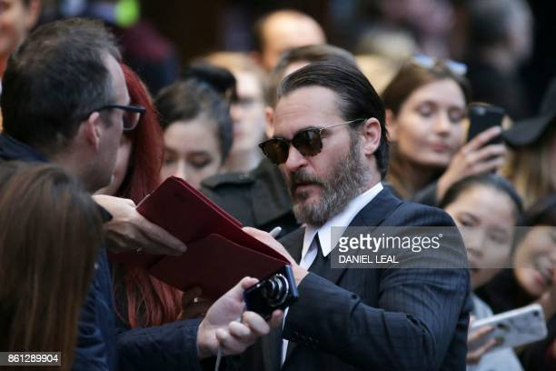 US actor Joaquin Phoenix signs autographs for fans on the red carpet arriving for the gala screening of the film 'You were Never really Here' during...
