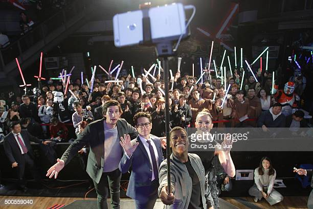 Actor John Boyega takes selfie with actor Adam Driver director JJ Abrams and actress Daisy Ridley during the event for fans ahead of 'Star Wars The...