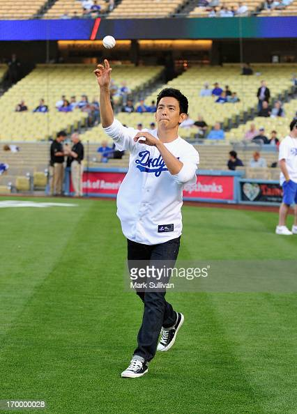 Actor John Cho warms up to throw out ceremonial first pitch before the game between the San Diego Padres and the Los Angeles Dodgers at Dodger...