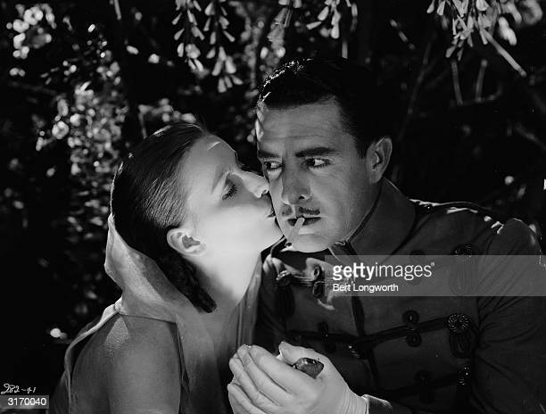 Actor John Gilbert receives a stolen kiss from Greta Garbo in a scene from 'Flesh and the Devil' directed by Clarence Brown