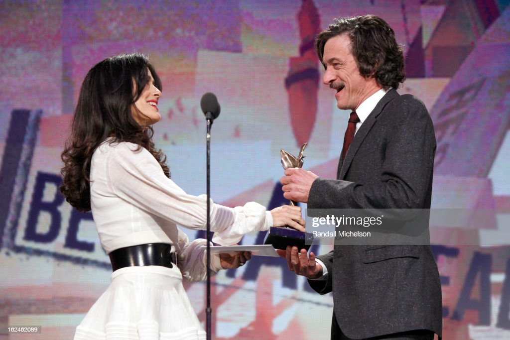 Actor <a gi-track='captionPersonalityLinkClicked' href=/galleries/search?phrase=John+Hawkes+-+Actor&family=editorial&specificpeople=224944 ng-click='$event.stopPropagation()'>John Hawkes</a> (R) accepts award from actress <a gi-track='captionPersonalityLinkClicked' href=/galleries/search?phrase=Salma+Hayek&family=editorial&specificpeople=201844 ng-click='$event.stopPropagation()'>Salma Hayek</a> (L) onstage during the 2013 Film Independent Spirit Awards at Santa Monica Beach on February 23, 2013 in Santa Monica, California.