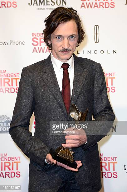 Actor John Hawkes poses with the Best Male Lead award for 'The Sessions' in the press room during the 2013 Film Independent Spirit Awards at Santa...