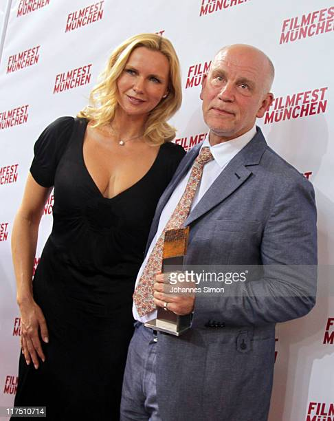 US actor John Malkovich poses with the CineMerit award trophy beside of German actress Veronica Ferres during the Muenchen Filmfest on June 27 2011...