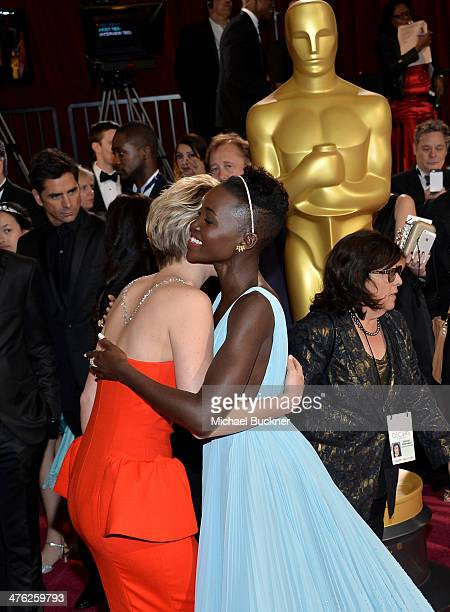 Actor John Stamos actresses Jennifer Lawrence and Lupita Nyong'o attend the Oscars held at Hollywood Highland Center on March 2 2014 in Hollywood...