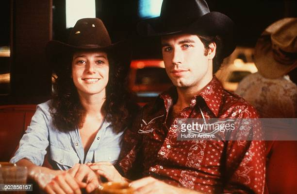 Actor John Travolta and Debra Winger smile on set of the Paramount Pictures movie 'Urban Cowboy' circa 1980