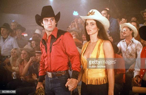 Actor John Travolta and Madolyn Smith Osborne walk in a scene of the Paramount Pictures movie 'Urban Cowboy' circa 1980
